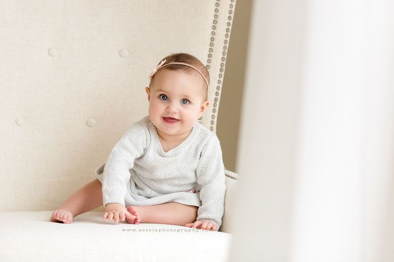 Studio photography session with baby girl posed on chair.