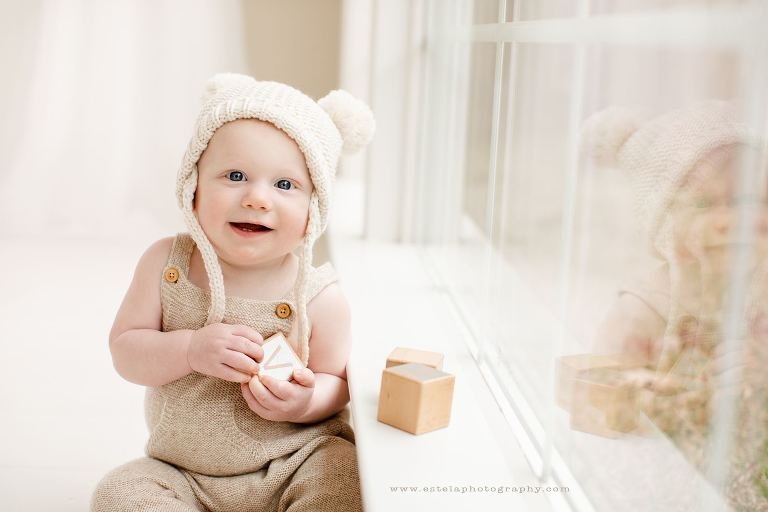 Photography studio images of baby boy by window wearing a hat.